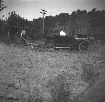 Two men, likely members of the Green family, are operating a plow attached to an automobile.  One man drives the car and the other guides the plow.