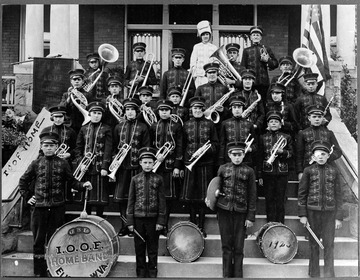 A group of unidentified boys pose in front of a building, wearing marching band uniforms and holding instruments.