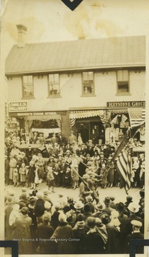 A group of soldiers march in the parade down High Street.  A cigar store and a grocery are visible in the background.