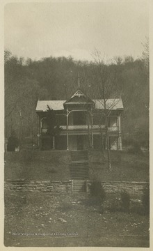 """""Holly Hall"" from the front. The stake shown in the foreground, at the bottom of the picture is Sta. 161 of our Location.""This photograph is found in a scrapbook documenting the survey for the Baltimore and Ohio Railroad in West Virginia and surrounding states."