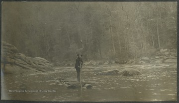 "A man identified as ""Dobbie"" stands on top of a raft as he makes his way across the river.This photograph is found in a scrapbook documenting the survey for the Baltimore and Ohio Railroad in West Virginia and surrounding states."
