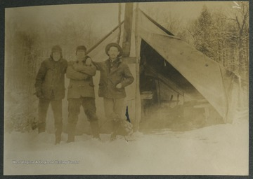 "Three men pose outside of a tent which has a ""comfortable"" interior, as described the photograph's inscription.This photograph is found in a scrapbook documenting the survey for the Baltimore and Ohio Railroad in West Virginia and surrounding states."