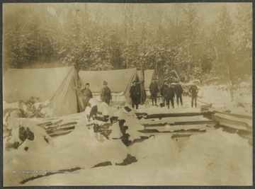 "Surveyors stand beside the tents and observe the ""Beautiful Snow !*?!!"".This photograph is found in a scrapbook documenting the survey for the Baltimore and Ohio Railroad in West Virginia and surrounding states."