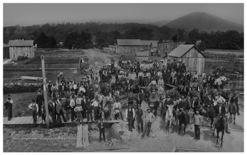 A mob returns to Parsons, W. Va. from the former seat of Tucker County, St. George.  The mob had taken records from the old courthouse by force.The view is from the corner of Main Street and Second Street, looking northeast down Second Street toward the Shavers Fork River and a treeline.  In the top right corner in the distance is a mountain called Turkey Knob.Ward Parsons, the leader of the mob, is pictured in the lower right on a black horse.