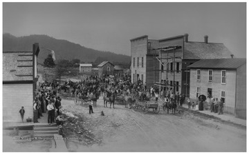 A mob returns to Parsons, W. Va. from the former seat of Tucker County, St. George.  The mob had taken records from the old courthouse by force.The view is from the corner of Main Street and Second Street, looking northwest down Main Street toward Alum Hill in the distance, which slopes downward to the right.There are two large buildings on the right.  The first one is under construction, and has scaffolding on it.  It was still standing in 2017 and houses the McClain Printing Co.  The second building, which is a little taller, is completed.  This building becomes the temporary courthouse, and the county records and furniture are put into it.  This building was torn down in 2007.