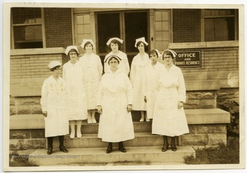 Eight nurses standing outside the Office and Private Residence of the Monongalia County Hospital.