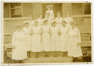 A group of nurses standing outside of Monongalia County Hospital, which was located on the corner of Willey and Prospect Streets in Morgantown.