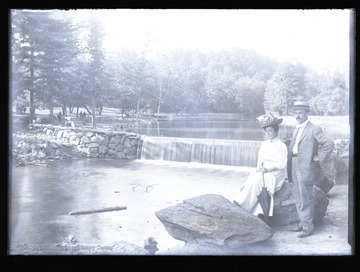 A couple poses near the dam, and others are visible on the left bank of the river.