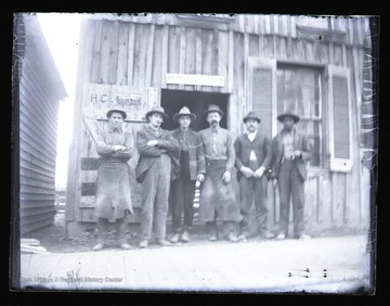 Workmen pose in front of a Franklin, W. Va. building.  The building has several signs on it, including one for Bickford & Huffman Grain Drills.  The men are likely blacksmiths.