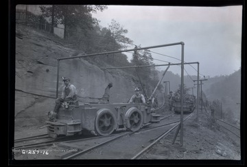Four men stand outside of mine with loaded mine car ready to be hitched to electric engine car in front.