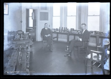 Two men sit next to a machine inside a Goodman Manufacturing Company showroom.