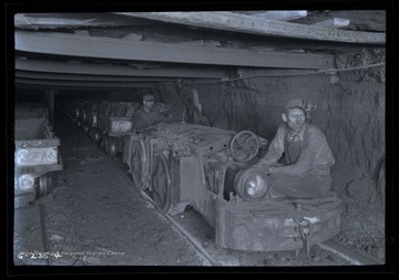 Two men ride on engine hauling loaded coal cars out of mine/
