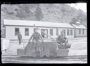 Two men sit on track mounted engine outside of mine