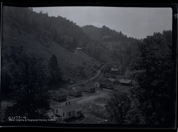 A row of houses sits next to railroad in a valley