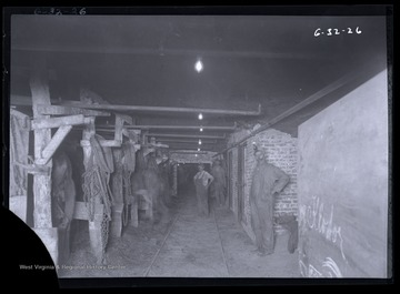 Three men pose for photo inside a mining stable, likely located underground.