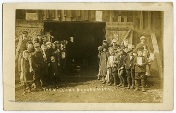 A group of children and some adults pose at the door of the blacksmith's shop at the south end of High Street.