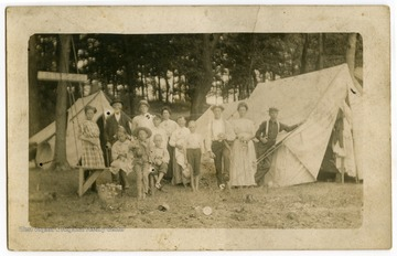 "A group of adults and children pose by their tents. A sign on a tree reads ""Floater's Rest."""