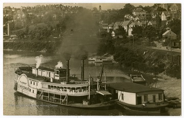 "The ""I. C. Woodward,"" launched in 1898 for the Pittsburgh, Brownsville, and Geneva Packet Company, and traveled between Pittsburgh and Morgantown. Woodburn Hall and Martin Hall can be seen on the bank in the background."