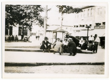 Men sit and talk in front of the courthouse on High Street. J. G. McCrory Co. can be seen in the background, now the site of Reeder and Shuman Attorneys at Law.
