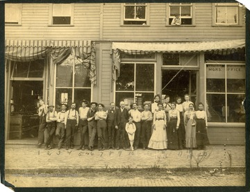 "Reverse reads:""This picture shows the staff of The Morgantown Printing and Binding Company.Number 1 is Gilbert Miller.Number 8 is H. A. Cristie.Number 9 is Mr. Ludwig, General Manager.The plant is located in the rooms now occupied by Benny the Tailor and Pikes Bakery on the north side of Pleasant Street, between High and Spruce."""