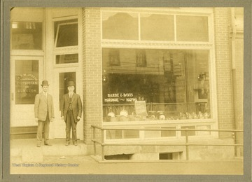 Two men stand outside the entrance to Barbe and Davis Hardware and the office of Dr. G. M. Joseph, Physician and Surgeon on Walnut Street.