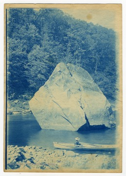 A man in a rowboat pauses by Squirrel Rock, which was submerged with the construction of the Cheat Lake Dam in 1926.