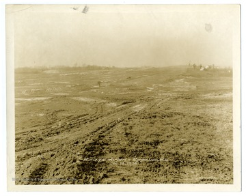 "Text on back reads, "" 'A' Runway from east side at Station 18 and 60. Rock base at north end being placed. Stock pile of surfacing materials."""