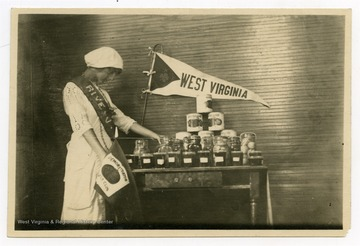 "Young woman pictured with display of 4-H Club items, holding flag that reads ""Demonstration Girls Club."""