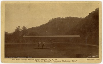 Two men pose in a boat in front of a covered bridge on the Cheat River.