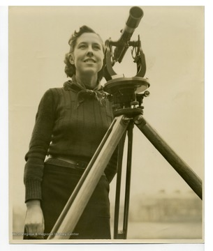 Esther Benford, the only woman student in West Virginia University College of Engineering at the time, with surveying scope.