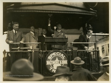 Franklin D. Roosevelt pictured standing at podium on Baltimore and Ohio train car.