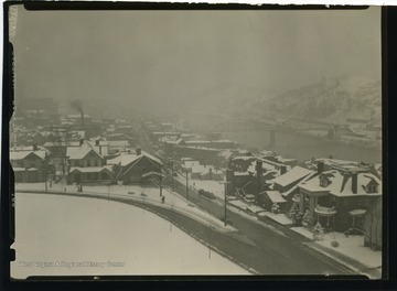 Photo features snow covered Morgantown, with the Westover Bridge in background.  The intersection of University Avenue and Willey Street is at the foreground.