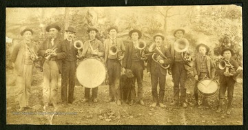 A brass ensemble from Webster Springs, made up of men and boys, poses in the woods with a dog.